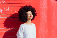 Afro Hair Woman Smiling While Standing In Front Of Red Wall
