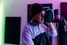 Man Wearing Knit Hat Singing At Home Studio