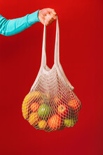 Arm Of Man Holding Reusable Cotton Mesh Bag With Fresh Fruits