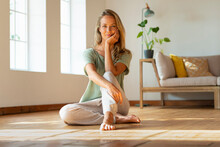 Beautiful Woman With Hand On Chin Sitting On Floor In Living Room