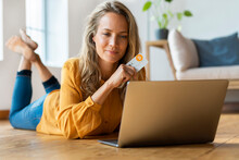Beautiful Mid Adult Woman Holding Bitcoin Credit Card While Looking At Laptop On Floor