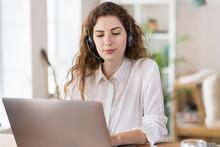 Beautiful Female Customer Service Representative Using Laptop At Home Office