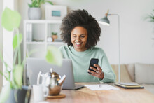 Smiling Woman With Mobile Phone Using Laptop At Home