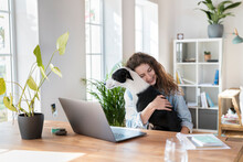 Smiling Female Professional With Eyes Closed Embracing Jack Russell Terrier At Home Office