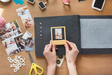 Woman Sticking Frame Over Dog Photo In Scrapbook