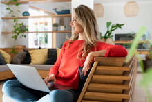 Smiling Blond Woman Sitting With Laptop On Couch In Living Room While Looking Away
