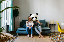 Woman Wearing Panda Mask Gesturing Peace Sign While Sitting With Girlfriend At Home