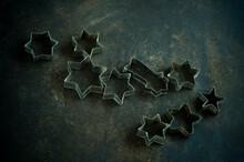 Star Shape Cookie Cutters On Rustic Baking Sheet