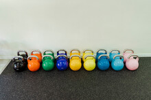 Arrangement Of Multi Colored Kettlebells In Health Club