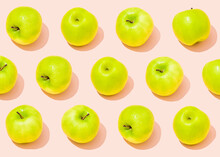 Pattern Of Green Apples Lying Against Light Pink Background
