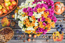 Autumn Harvest Including Bouquet Of Blooming Chrysanthemums, Various Nuts, Apples, Pumpkin, Plums And Grape Leaves