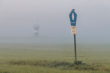 Road Sign Standing At Edge Of Meadow Shrouded In Fog