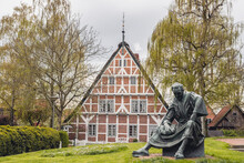 Germany, Altes Land, Half Timbered House With Statue Of Priest Heinrich Von Carsten Eggers In Foreground