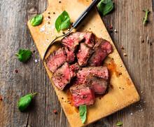 Basil, Fork, Peppercorns And Steak Lying On Cutting Board