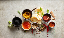Studio Shot Of Naan Bread, Chili Dipping Sauce And Bowls With Various Masala Spices