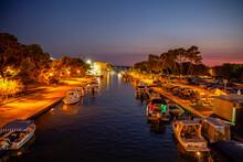Croatia, Split-Dalmatia County, Trogir, Motorboats Moored Along Illuminated City Canal At Night