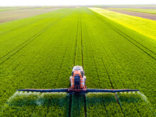 Tractor Spraying Fertilizer On Agricultural Field