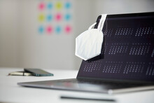 Protective Face Mask Hanging On Laptop Screen At Desk In Office