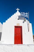 Whitewashed Church With Greek Flag In Mykonos, Greece