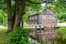 Finland, Raseborg, Bridge Over River Flowing Through Public Park With Traditional House In Background