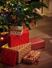 Wrapped Gifts In Front Of Christmas Tree At Home
