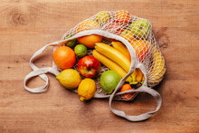 Reusable Cotton Mesh Bag With Fresh Fruits Lying On Wooden Table