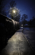 Street Light Illuminating Empty Sidewalk At Winter Night