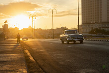 Vintage Cars Driving At Sunrise On Malecon In Havanna