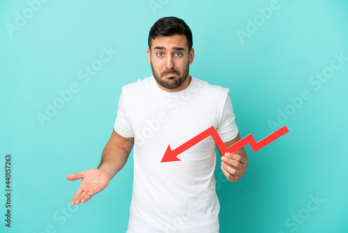 Slika na platnu Young handsome caucasian man isolated on blue background holding a downward arro