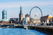 Germany, Dusseldorf, Architecture And Ferris Wheel On Riverbank