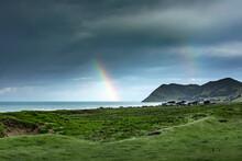 Double Rainbow Piercing Dark Storm Clouds Over Green Coastal Terrain