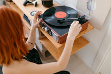 Unrecognizable Woman Turning On Turntable With Vinyl Record At Home