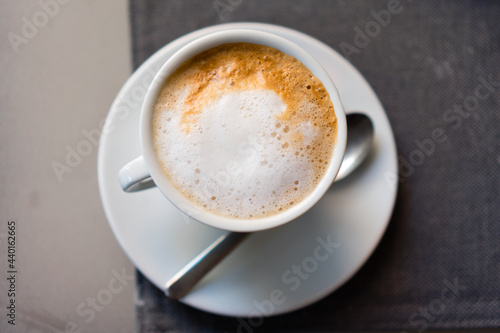 Stampa su Tela Top view of a cup of fresh cappuccino on a table