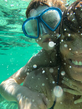 Mother With Young Boy Wearing A Snorkelling Mask, On Her Back Underwater Looking At The Camera
