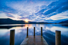 Vibrant Sunset Wooden Jetty At Derwentwater Lake In The Lake District, UK.