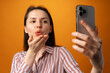Leinwandbild Motiv Portrait of young attractive woman using her smartphone against yellow background