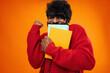 Leinwandbild Motiv Successful african american male student holding books against orange background