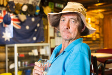 A Elderly Man Sitting In An Outback Pub Holding A Glass To His Chest