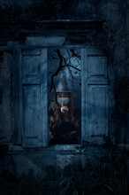Halloween Witch Wearing Medical Face Mask Showing Silence Sign With Finger Over Lips Standing In Old Damaged Wood Window With Wall Over Cross, Church, Birds, Dead Tree And Spooky Cloudy Sky, Halloween