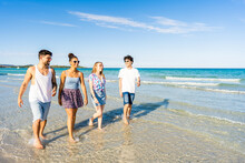Multicultural Friends Walking In Summer Beach Vacation In Crystal Clear Water Of Tropical Ocean Sea Resort Smiling Wearing Casual Clothes. Multiracial Millennial Happy People Enjoying Life In Nature