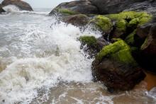 Foamy Waves Of The Ocean Hitting Mossy Rocks