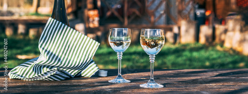 Canvas Two glasses of white wine and a bottle on an old wooden table in the courtyard o