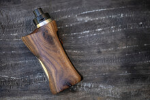 High End Rebuildable Dripping Atomizer With Stabilized Natural Walnut Regulated Box Mods On Dark Old Wood Texture Background, Vaping Device, Selective Focus