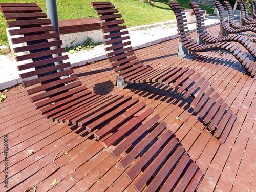 Fotografia, Obraz Closeup shot of a row of wooden sun loungers