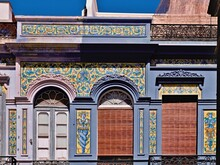 Frontal Art Nouveau Facade, Richly Decorated With Painted Tiles, In Santa Cruz De Tenerife. The Doors Have Round Arches And Glass Decorations, The Tiles Are In Yellow And Blue And Show Angels