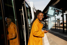 Smiling Woman Leaving Bus At Bus Station With Covid-19 Vaccine Certificate On Cell Phone