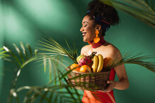 Smiling Young African American Woman In Red Swimsuit Holding Basket With Exotic Fruits On Green
