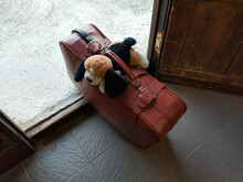 An Old Brown Suitcase With A Plush Toy On It Stands At The Exit From The House