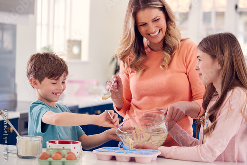 Wallpaper Mural Mother With Two Children In Kitchen At Home Having Fun Baking Cakes Together