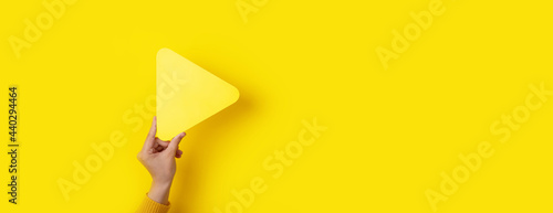 Fotografie, Obraz media player button in hand over yellow background, panoramic mockup